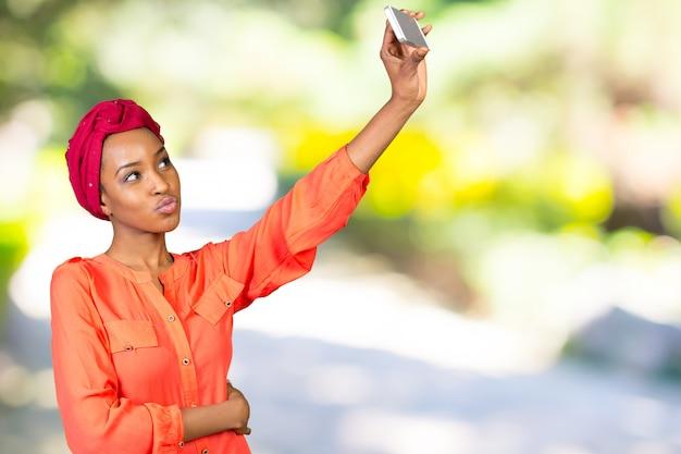 Portret uśmiechnięta afro amerykańska kobieta robi selfie fotografii