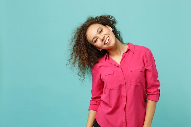 Portret uśmiechnięta afrykańska dziewczyna w ubranie stojące z trzepotliwymi włosami na białym tle na tle niebieskiej ściany turkus w studio. ludzie szczere emocje, koncepcja stylu życia. makieta miejsca na kopię.