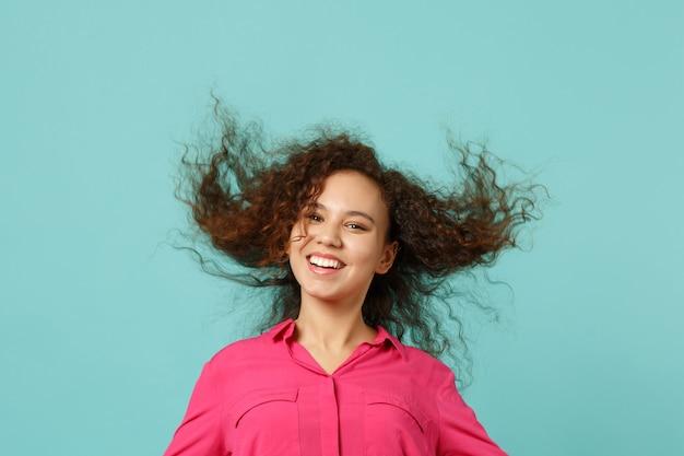 Portret uśmiechnięta afrykańska dziewczyna w ubranie stojące z włosami na białym tle na tle niebieskiej ściany turkus w studio. ludzie szczere emocje, koncepcja stylu życia. makieta miejsca na kopię.