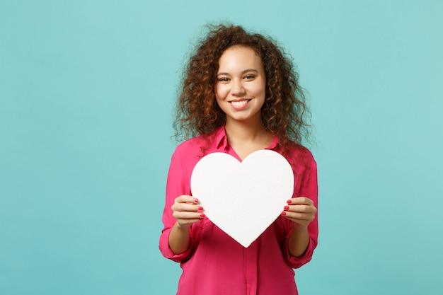 Portret uśmiechnięta afrykańska dziewczyna w ubranie trzyma białe serce z kopią przestrzeni na białym tle na niebieskim turkusowym tle. ludzie szczere emocje, koncepcja stylu życia. makieta do reklamy.