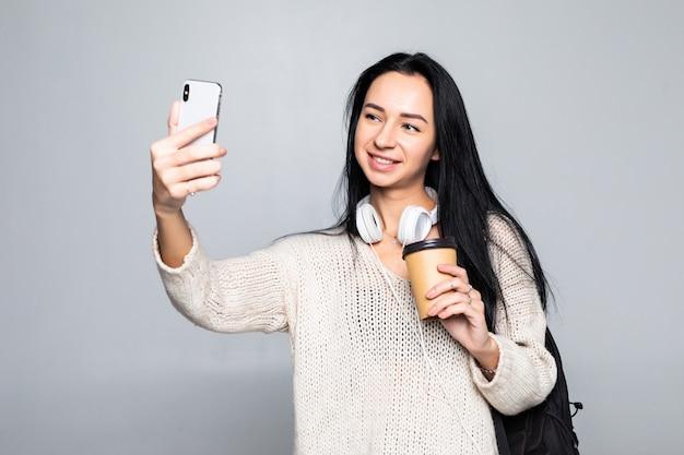 Portret uśmiechnięta atrakcyjna kobieta bierze selfie podczas gdy trzymający bierze oddaloną filiżankę odizolowywającą nad biel ścianą
