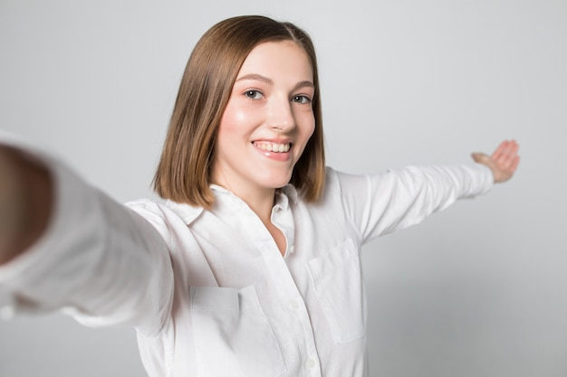Portret uśmiechnięta atrakcyjna kobieta biorąc selfie, podczas gdy na białym tle nad białą ścianą