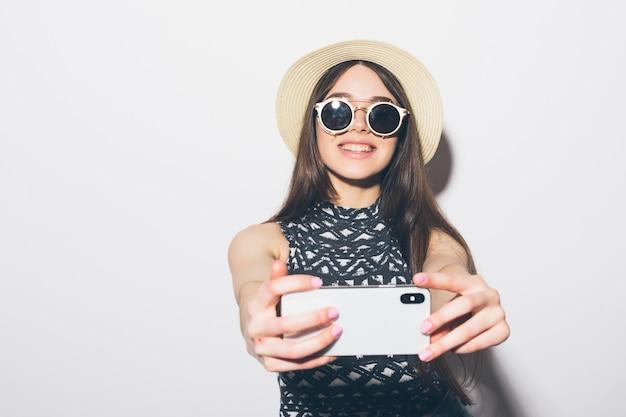 Portret uśmiechnięta atrakcyjna kobieta w kapeluszu stojąc i biorąc selfie na białym tle