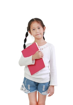 Portret uśmiechnięta azjatycka mała dziewczynka trzyma książkę na białym tle na białej ścianie