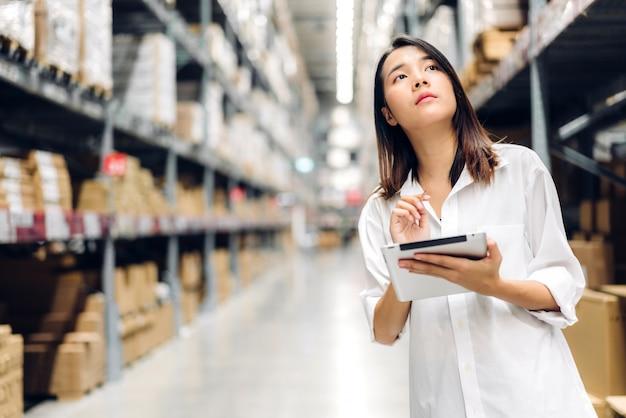Portret uśmiechnięta azjatycka menedżer kobieta pracownik stojący i szczegóły zamówienia na komputerze typu tablet do sprawdzania towarów i dostaw na półkach z tłem towarów w magazynie
