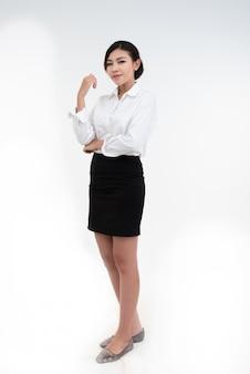 Portret uśmiechnięta azjatykcia bizneswoman pozycja z rękami składał i patrzeje kamerę odizolowywającą nad bielem