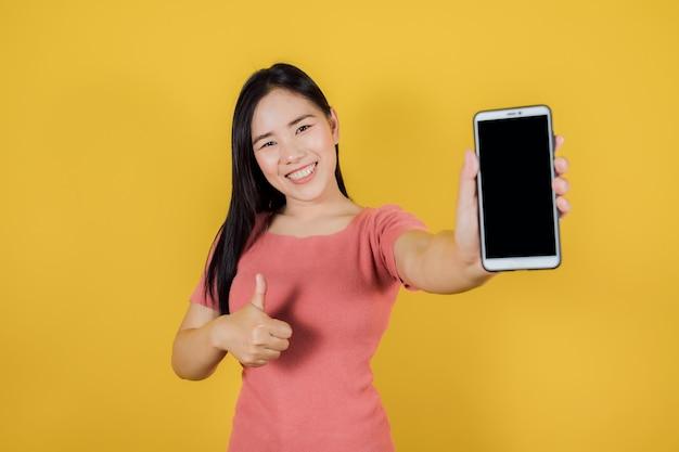 Portret uśmiechnięta azjatykcia kobieta pokazuje pusty ekran telefon komórkowy stojąc na żółtym tle.