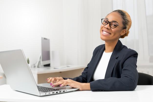 Portret uśmiechnięta biznesowa amerykanin afrykańskiego pochodzenia kobieta pracuje na komputerze.