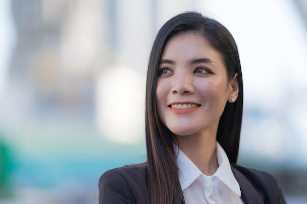 Portret uśmiechnięta biznesowa kobieta stojąc przed nowoczesnymi budynkami biurowymi