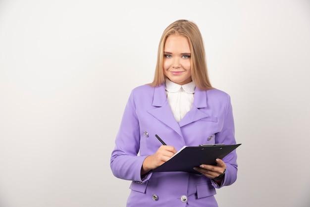 Portret uśmiechnięta biznesowa kobieta stojąca i trzymająca schowek.