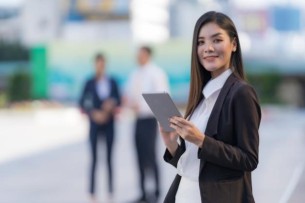 Portret uśmiechnięta biznesowa kobieta trzyma cyfrowy tablet stojący przed nowoczesnymi biurowcami