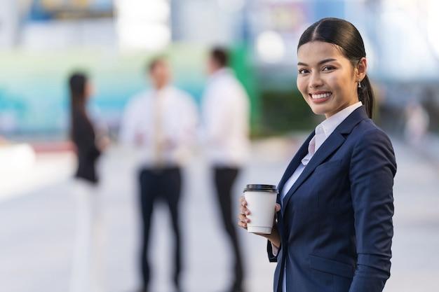 Portret uśmiechnięta biznesowa kobieta trzyma filiżankę kawy, stojąc przed nowoczesnymi budynkami biurowymi