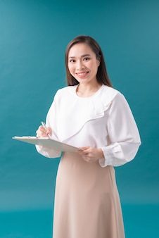 Portret uśmiechnięta biznesowa kobieta z pióro i papierową falcówką. młoda ładna pracownica pisze coś w swoich papierach