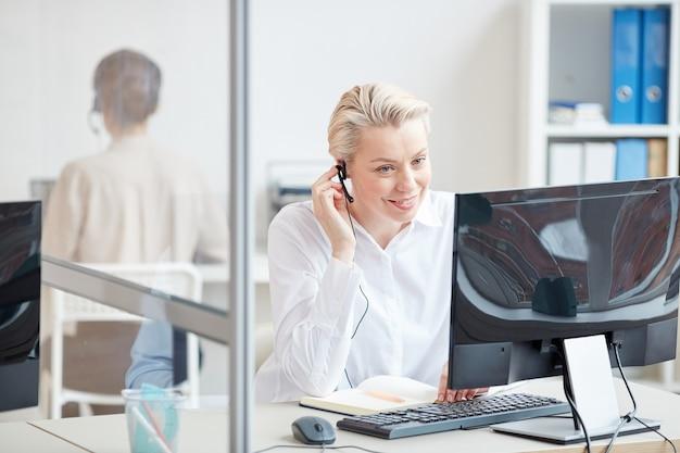 Portret uśmiechnięta bizneswoman mówi do mikrofonu podczas korzystania z komputera w wnętrz biurowych, koncepcja obsługi klienta