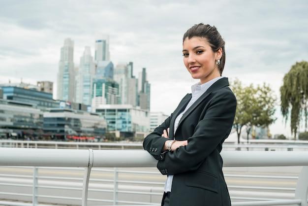 Portret uśmiechnięta bizneswoman pozycja przed pejzażem miejskim