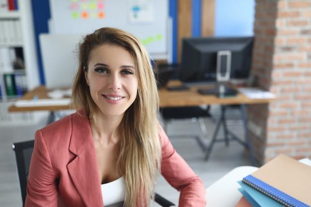 Portret uśmiechnięta bizneswoman w miejscu pracy w biurze