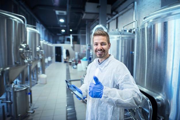 Portret uśmiechnięta blond technolog w białym mundurze trzymając tabletkę i kciuki do góry.