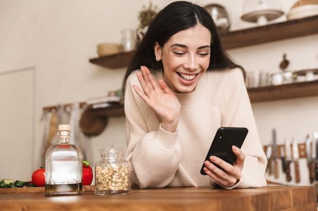 Portret uśmiechnięta brunetka kobieta trzymając smartfon podczas gotowania zielonej sałatki z warzywami w stylowej kuchni w domu