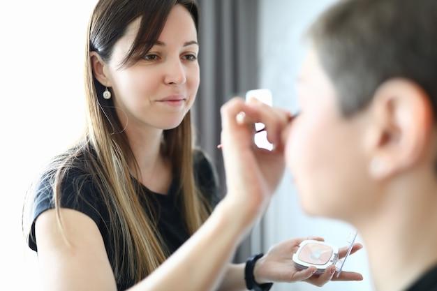 Portret uśmiechnięta brunetka patrząc na klientkę z radością. visagiste robi makijaż