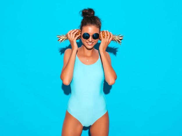Portret uśmiechnięta brunetki dziewczyna w lata swimwear kostiumu kąpielowym i okularach przeciwsłonecznych. seksowna kobieta z świeżymi małymi ananasami. pozytywny model pozowanie w pobliżu niebieską ścianą. trzymać go w pobliżu uszu
