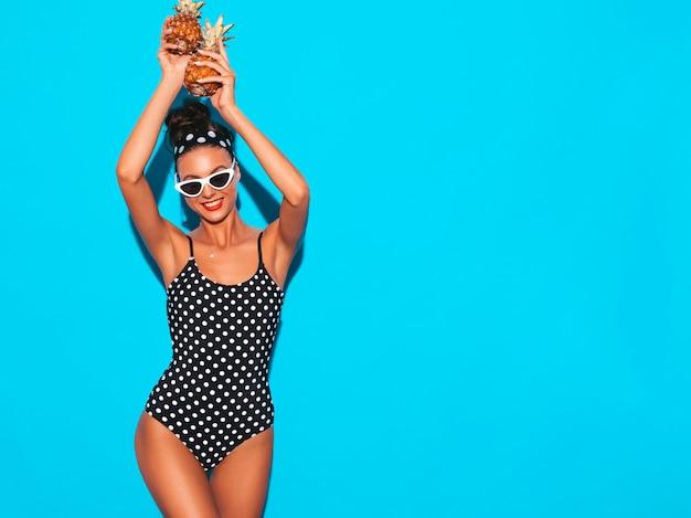 Portret uśmiechnięta brunetki dziewczyna w lato grochu stroju kąpielowego kostiumie kąpielowym i okularach przeciwsłonecznych.