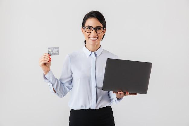 Portret uśmiechnięta businesswoman noszenia okularów, trzymając srebrny laptop i kartę kredytową w biurze, odizolowane na białej ścianie