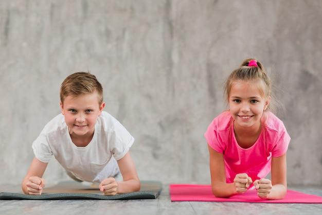 Portret uśmiechnięta chłopiec i dziewczyna robi sprawności fizycznej ćwiczeniu przed betonową ścianą