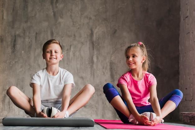 Portret uśmiechnięta chłopiec i dziewczyna siedzi wpólnie ćwiczyć przeciw betonowemu tłu