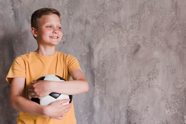 Portret uśmiechnięta chłopiec mienia piłki nożnej piłka przed betonową ścianą