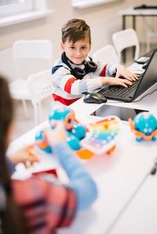 Portret uśmiechnięta chłopiec patrzeje kamerę z laptopem na biurku