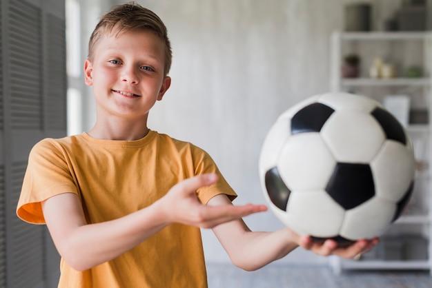 Portret uśmiechnięta chłopiec pokazuje piłki nożnej piłkę