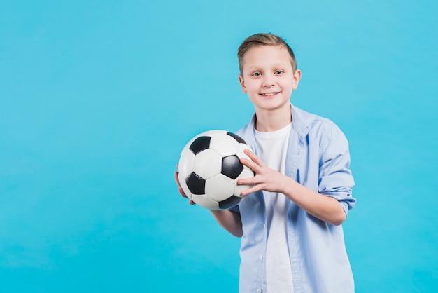 Portret uśmiechnięta chłopiec trzyma piłki nożnej piłkę w ręku stoi przeciw niebieskiemu niebu