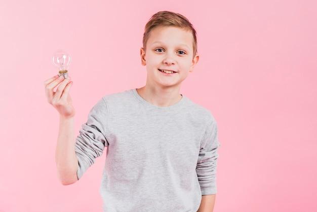 Portret uśmiechnięta chłopiec trzyma żarówkę w ręki pozyci przeciw różowemu tłu