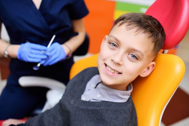 Portret uśmiechnięta chłopiec w stomatologicznym krześle.