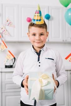Portret uśmiechnięta chłopiec z strona kapeluszem na jego mienia mieniu zawijającym teraźniejszym pudełku