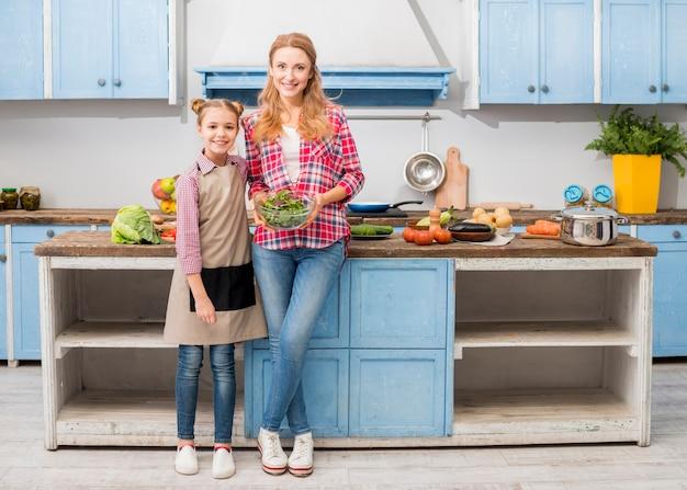 Portret uśmiechnięta córki pozycja z jej macierzystym mienia pucharem sałatka