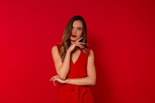 Portret uśmiechnięta czarująca kobieta w czerwonej sukience pozowanie