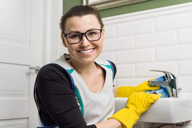 Portret uśmiechnięta dorosła kobieta robi domowemu cleaning