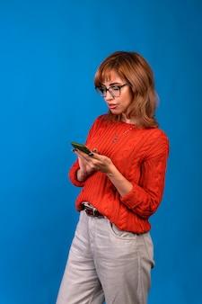 Portret uśmiechnięta dorywczo kobiety trzymającej smartfon na niebieskim tle.