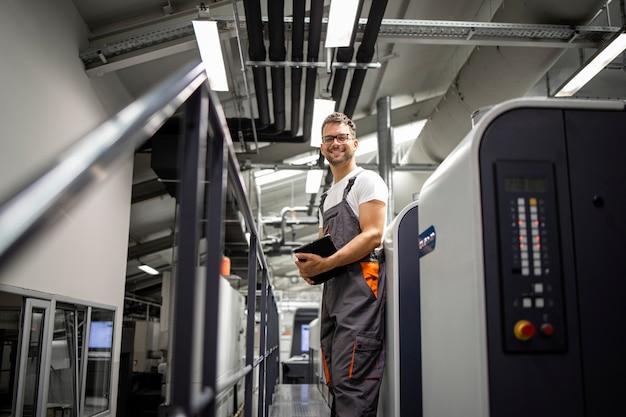Portret uśmiechnięta drukarka stojąca przy maszynie drukarskiej w drukarni.