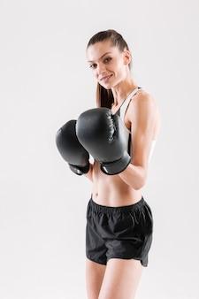 Portret uśmiechnięta dysponowana sportsmenka w rękawiczkach bokserskich
