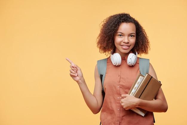Portret uśmiechnięta dziewczyna afro-amerykańskiego studenta z książkami, wskazując na bok, zalecając szkołę internetową
