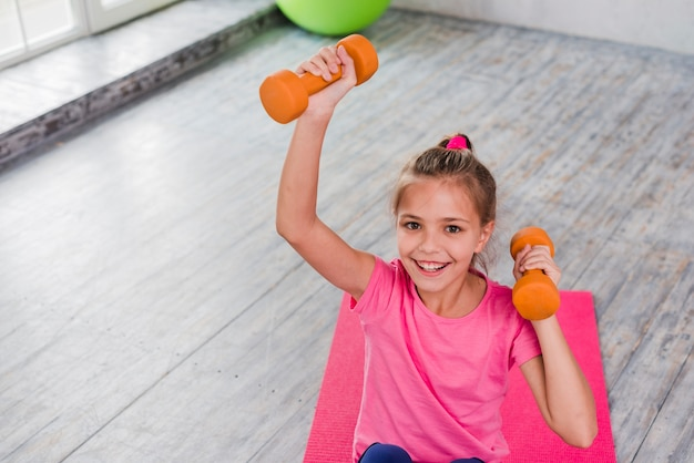 Portret uśmiechnięta dziewczyna ćwiczy z pomarańczowym dumbbell