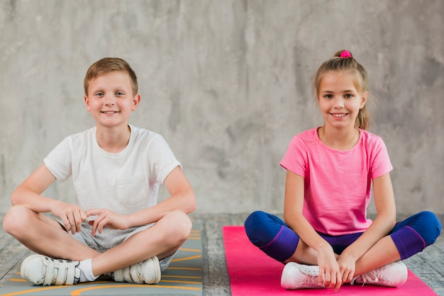 Portret uśmiechnięta dziewczyna i chłopak siedzi na matę do ćwiczeń z ich skrzyżowanymi nogami przed ścianą