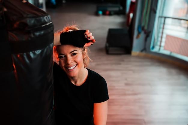 Portret uśmiechnięta dziewczyna opiera na worku treningowym. patrząc na aparat.