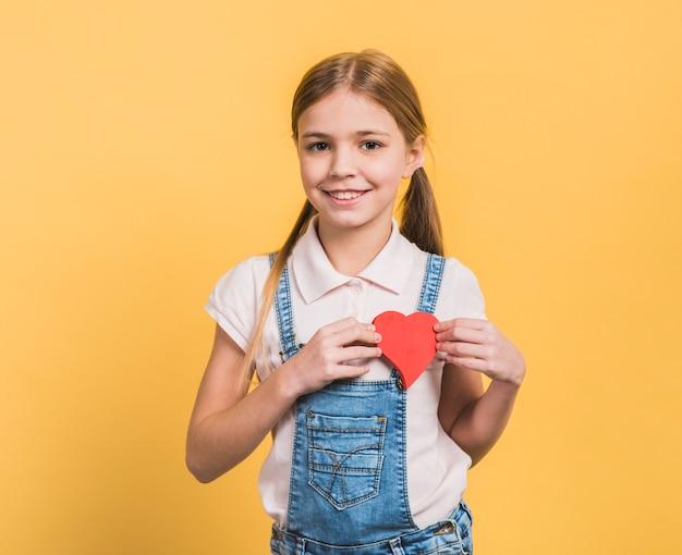 Portret uśmiechnięta dziewczyna pokazuje czerwonego papier ciie out kierowego kształt przeciw żółtemu tłu