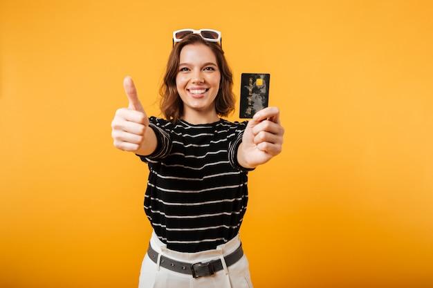 Portret uśmiechnięta dziewczyna trzyma kredytową kartę