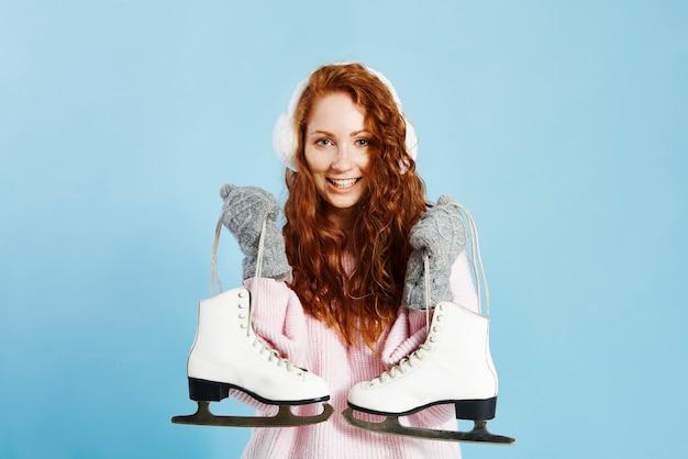 Portret uśmiechnięta dziewczyna trzyma łyżwy