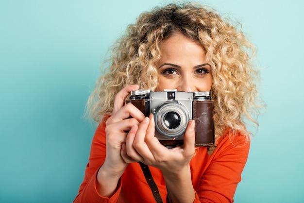 Portret uśmiechnięta dziewczyna trzyma rocznika aparat