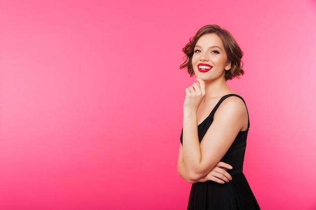 Portret uśmiechnięta dziewczyna ubrana w czarną sukienkę